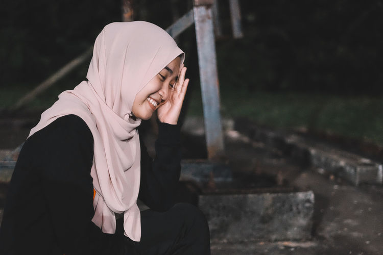 Smiling woman wearing hijab at park