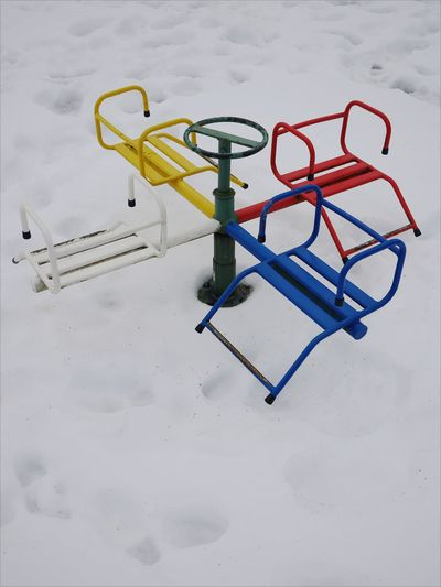 High angle view of colorful metallic outdoor play equipment at playground during winter