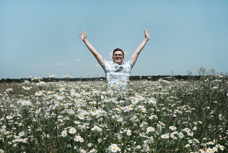 Man with arms outstretched standing amidst daisy flowers blooming on field