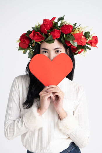 Make funny faces with flower,Love concepts Love Heart Shape Woman Rose - Flower Cute Valentine's Day  Funny Cheerful Fashion Lifestyles Eyes Happiness Holding Portrait Studio Shot