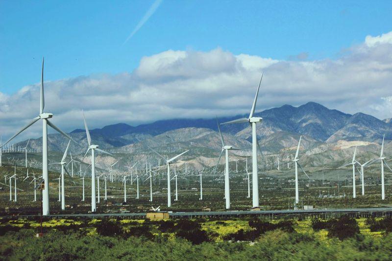 Wind turbines on land against sky