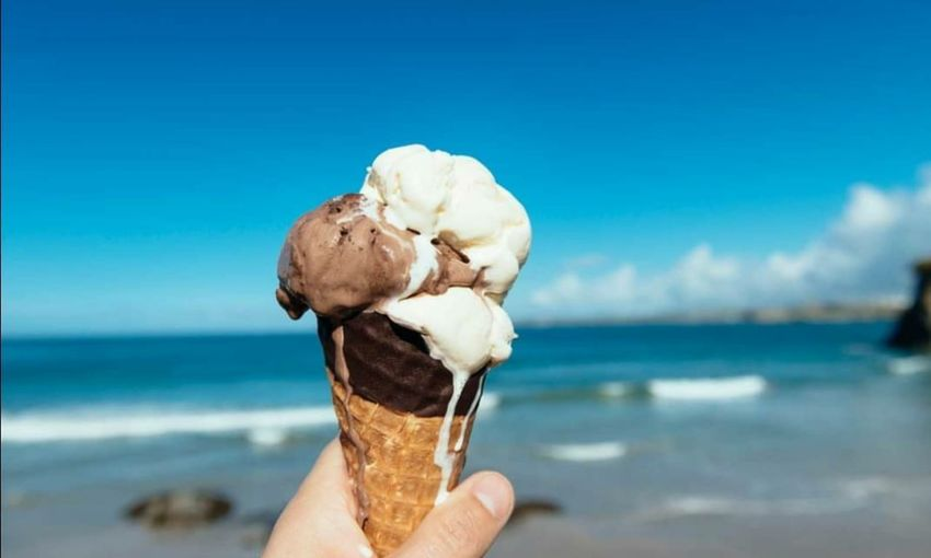 Close-up of hand holding ice cream cone at beach