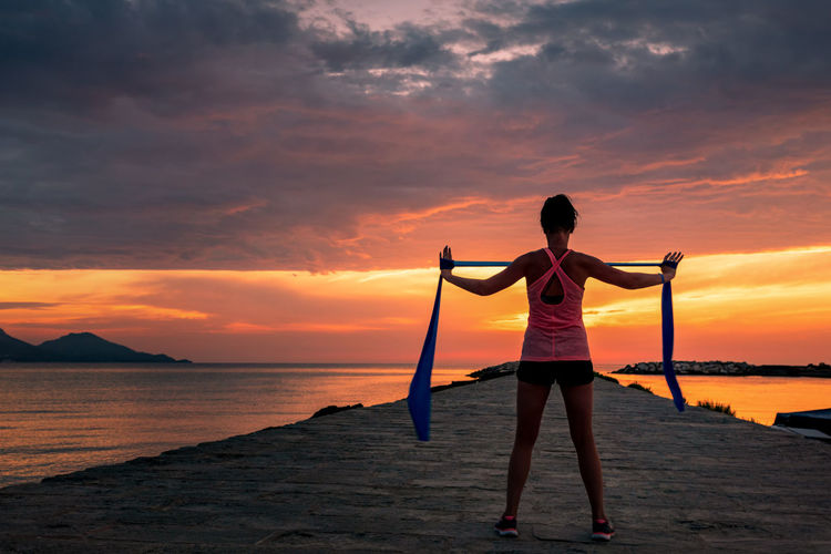 Fitness woman celebrating fitness workout with rubber band - success and motivation towards the sea and sunset or sunrise. Sunset Sky Water One Person Real People Beauty In Nature Lifestyles Scenics - Nature Sea Beach Cloud - Sky Land Leisure Activity Standing Rear View Orange Color Full Length Nature Human Arm Arms Outstretched Horizon Over Water Outdoors Arms Raised Women Workout Fitness Yoga Success Motivation