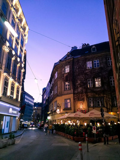 City street amidst buildings against clear sky at dusk