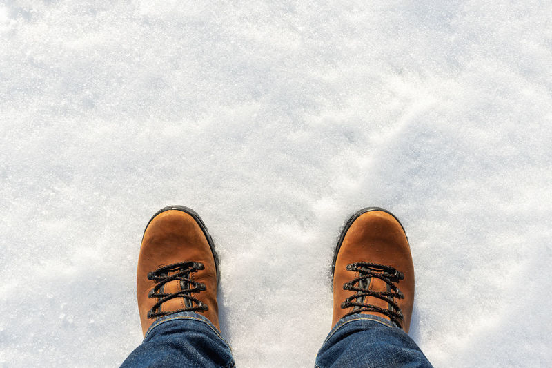 Low section of person standing on snow