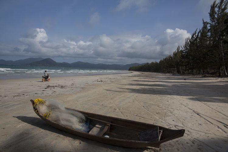 Fishing boat moored at padang melang beach against sky