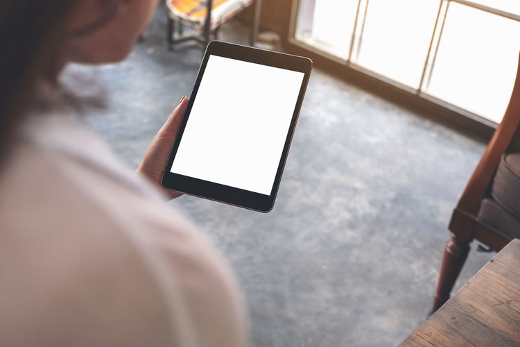 Midsection of woman holding digital tablet while sitting at cafe