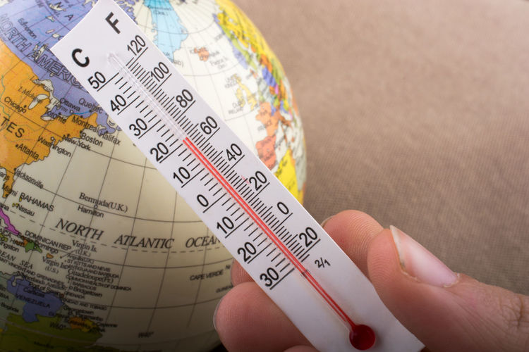 Cropped hand holding thermometer over globe
