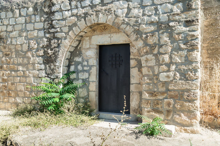 Bar'am, Israel, June 09, 2018 : Side door in the functioning church of the Christian Maronites in the abandoned village Kafr Birim in the north of Israel Christian Maronites Church Cross God Jesus Christ Kafr Birim Abandoned Village Arabic Architecture Art Belfry Tower Bible Building Culture Day Heritage History Holy Israel Landmark Monument Old Pry Religion Symbol
