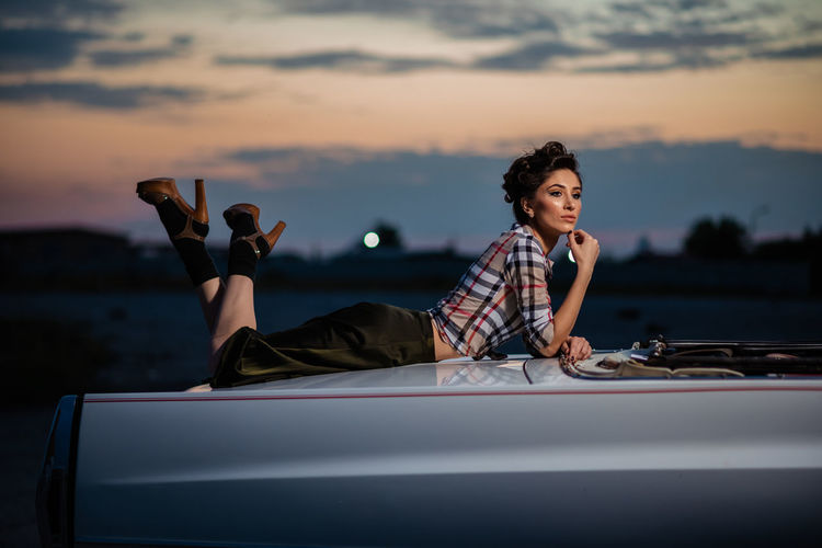 Woman sitting on car against sky during sunset