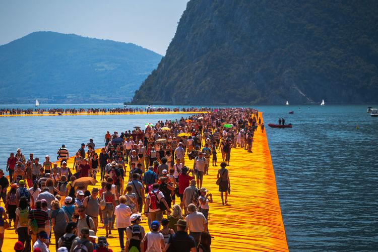 People on boardwalk in sea against mountains