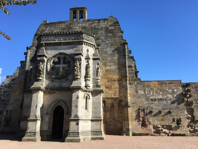 Rosslyn Chapel Architecture Built Structure History Building Exterior Low Angle View Religion Spirituality Blue Place Of Worship Outdoors Day Tourism Sunlight Travel Destinations Ancient Clear Sky Sculpture Statue No People Travel