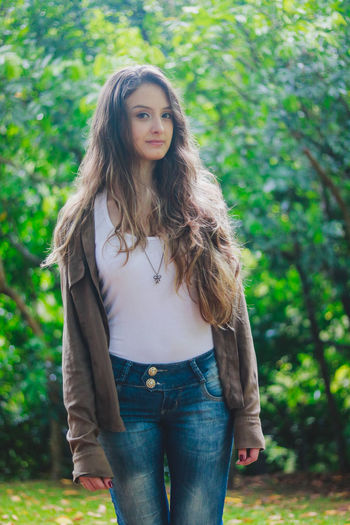 Beautiful Woman Casual Clothing Day Focus On Foreground Front View Leisure Activity Lifestyles Long Hair Looking At Camera Nature One Person Outdoors Portrait Real People Standing Tree Young Adult Young Women