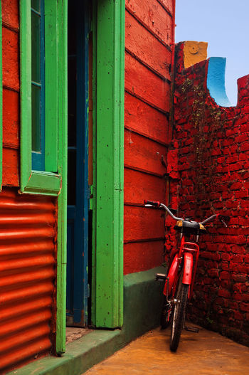 A red bicycle resting against a red wall in Buenos Aires, Argentina. Architecture Argentina Bicycle Bike Blue Boca Bricks Buenosaires Building Color Colorful Culture Day Door Exterior Green House Neighborhood Outdoors Red Tango Vibrant View Wall Wood