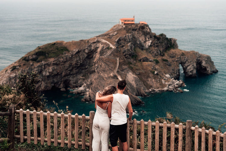 Rear view of couple standing by railing over sea