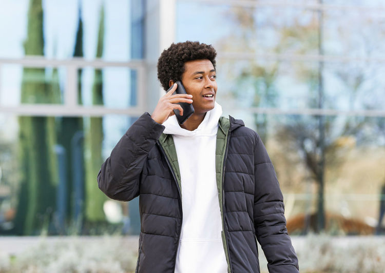 Young man looking away while standing on mobile phone