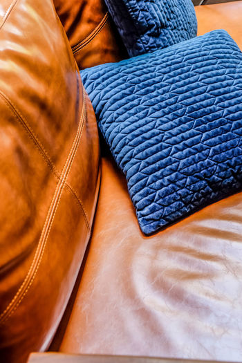 Close up detail of blue pillow on leather sofa Decor Leather Living Orange Pillow Backgrounds Blue Brown Casual Clothing Close-up Clothing Cushion Decoration Decorations Decorative Fashion Full Frame Furniture Furniture Details High Angle View Home Interior Indoors  Interior Design Jeans Leather Leather Sofa Living Room Material Menswear No People Orange Color Pattern Shoe Sofa Softness Still Life Textile Textured  Warm Clothing