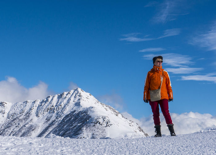 Woman standing on snow covered mountain against sky
