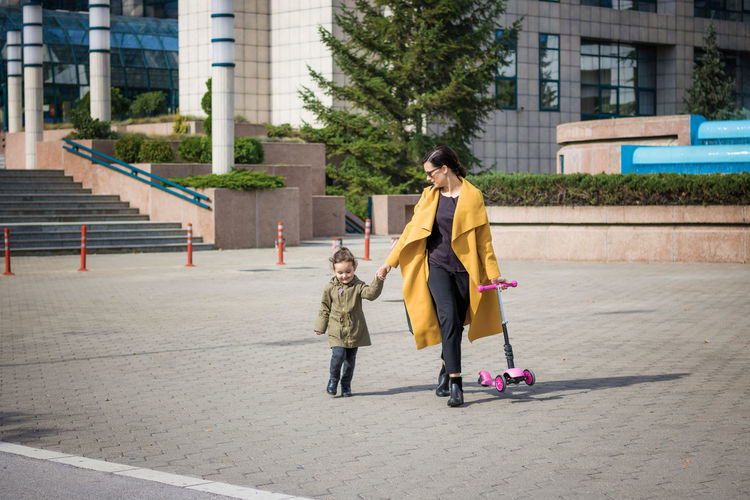 Full length of mother and daughter walking on paving stone in city