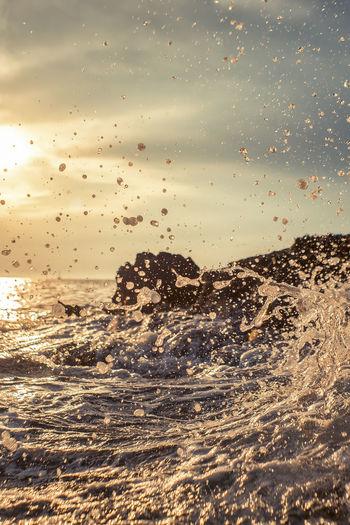 Water splashing in sea against sky during sunset