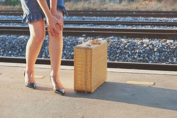 Young pretty female traveler massaging her knee in leg ache gesture with bamboo suitcase on railway platform at train station during travel by train concept Travel Space Lifestyle Tourist Massaging Pain Ache Legs Achy Bamboo Suitcase Vintage Female Traveler Low Section Standing Young Women Sunlight Shadow Human Leg Shoe Railroad Track Railroad Station Platform Railroad Station Public Transportation Railroad Platform Passenger Train Shining Personal Perspective