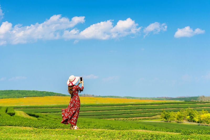 Woman standing on green grass in green tea field. Agriculture Beauty In Nature Cloud - Sky Cultivated Land Day Farm Field Grass Growth Landscape Lifestyles Nature One Person Outdoors Real People Rice Paddy Rural Scene Scenics Sky Standing Tranquil Scene Tranquility Women Young Adult Young Women