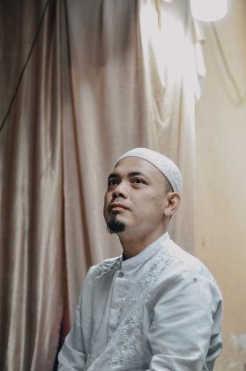 Man wearing skull cap while looking away