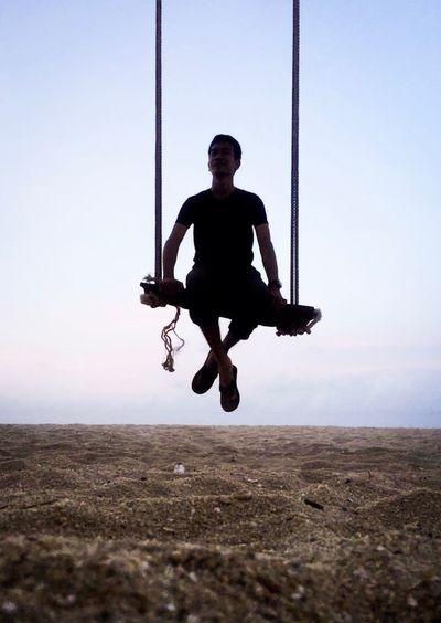 Full length portrait of man swinging against clear sky