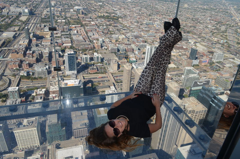 Young woman on glass elevator against cityscape