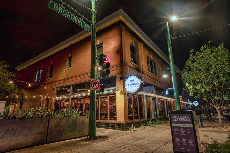 Illuminated street light by building at night