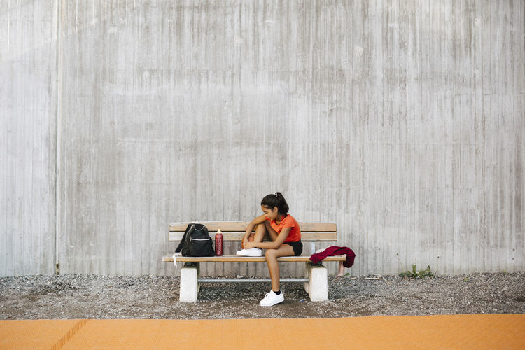 Full length of woman sitting on bench against wall