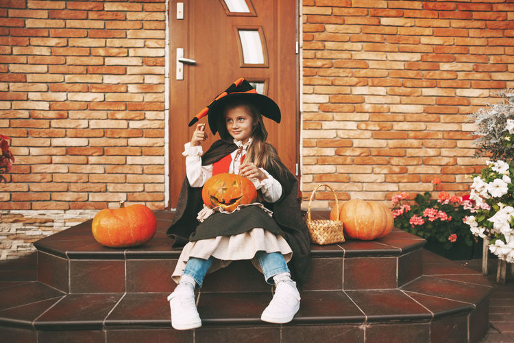 Portrait of smiling girl holding pumpkin against brick wall