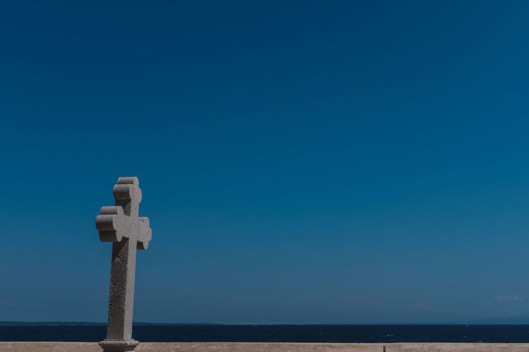 Cross by sea against clear blue sky
