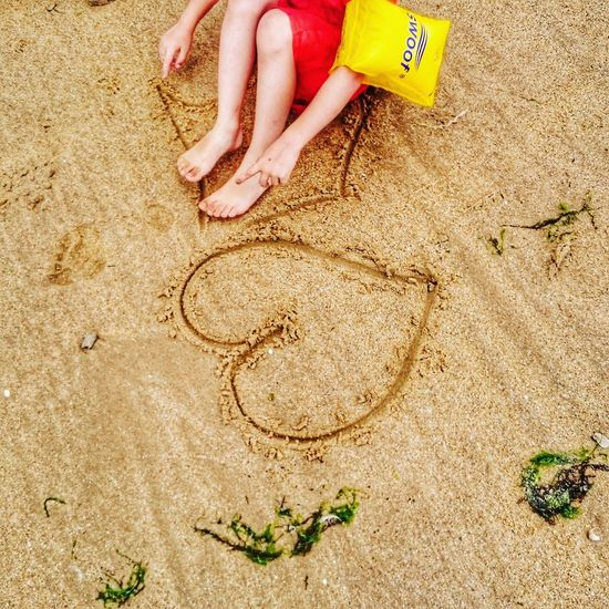 High angle view of child playing on sand at beach