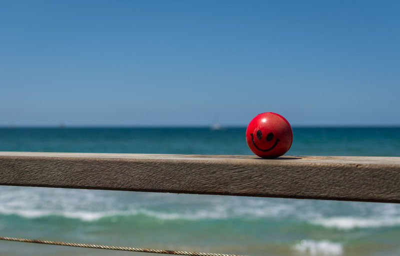 Red stress ball on wooden railing against sea