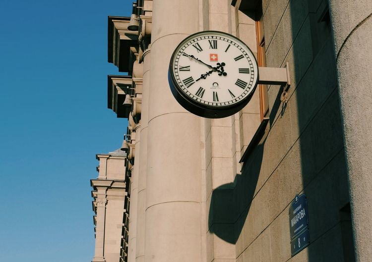 Low angle view of clock on wall against building