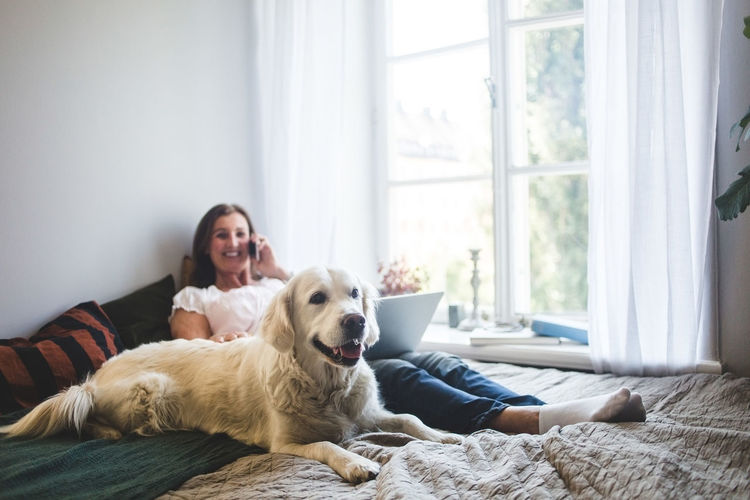Woman with dog sitting by window