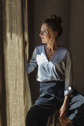 Woman looking away while sitting on window