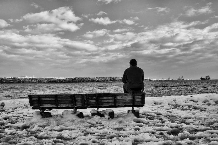 Rear view of man sitting on bench at beach