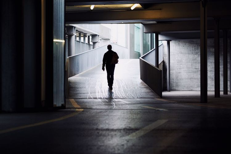 Rear view of man walking in basement