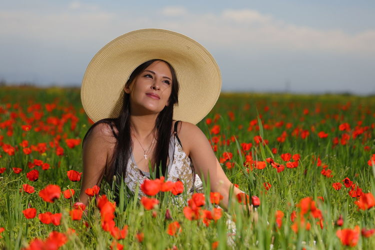Portrait of beautiful young woman with red flowers in field