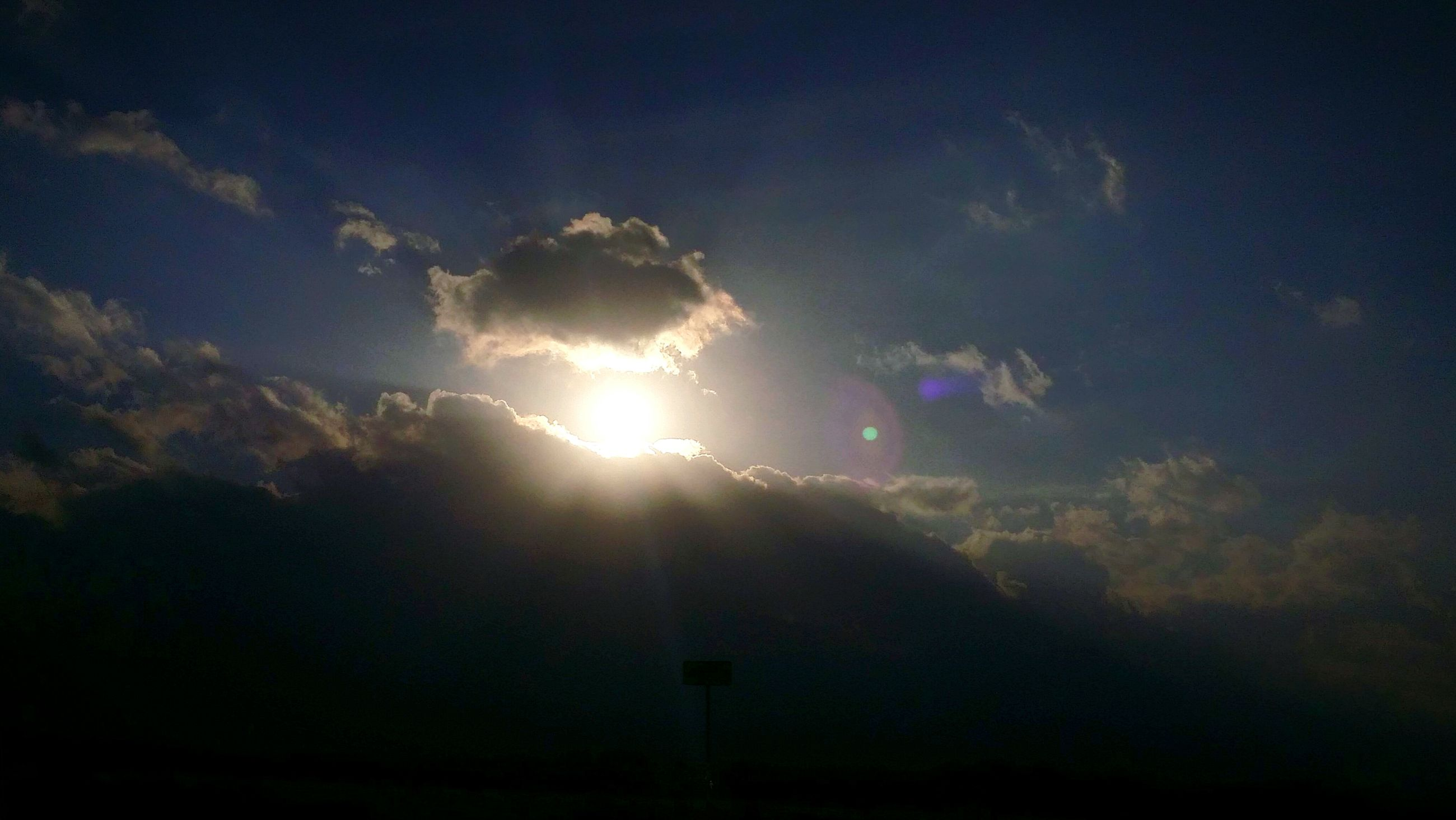 sky, sun, sunbeam, cloud - sky, low angle view, sunlight, silhouette, beauty in nature, lens flare, scenics, nature, tranquility, cloud, cloudy, tranquil scene, blue, outdoors, no people, weather, dark