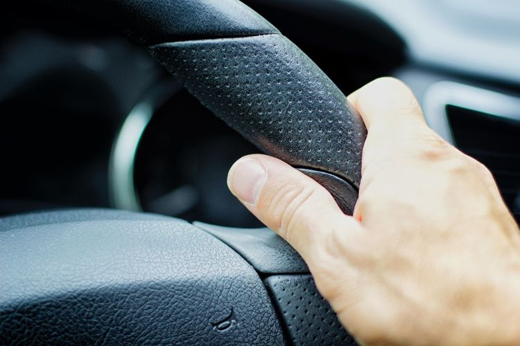 Cropped hand holding car steering wheel