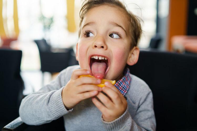 Close-up of boy licking lemon at home