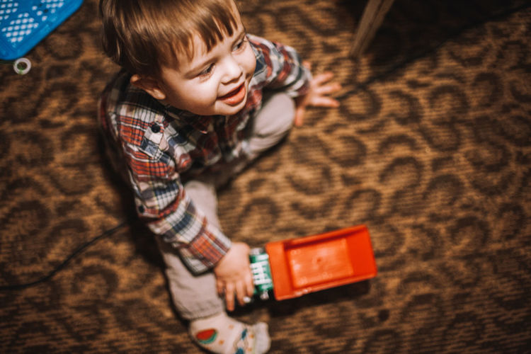 High angle view of boy playing with toy while sitting on carpet