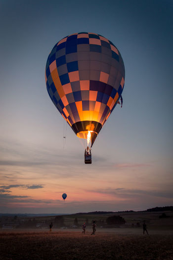 Hot Air Balloon Flying Over Land During Sunset