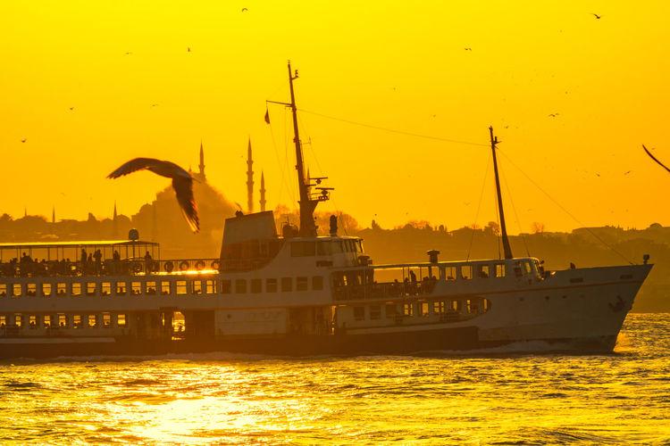 Nautical vessel in sea against orange sky