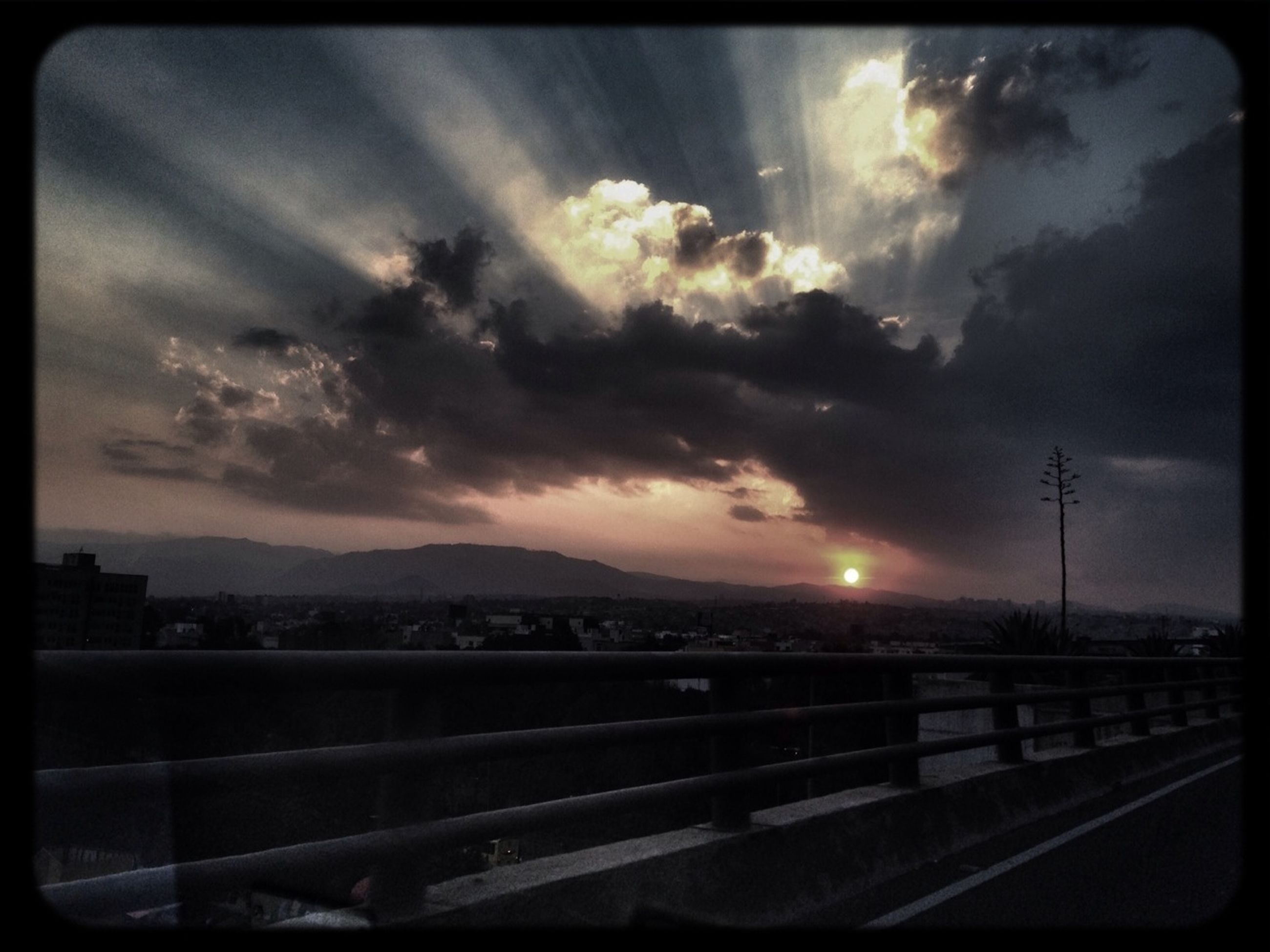 sky, transfer print, cloud - sky, cloudy, sunset, auto post production filter, street light, cloud, transportation, road, railing, scenics, dusk, nature, mountain, beauty in nature, connection, weather, dramatic sky, overcast