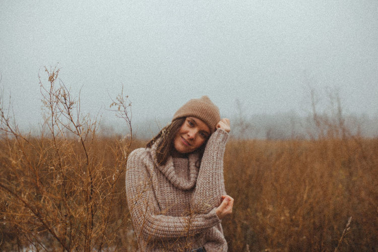Woman wearing beanie on foggy field against sky during late autumn winter