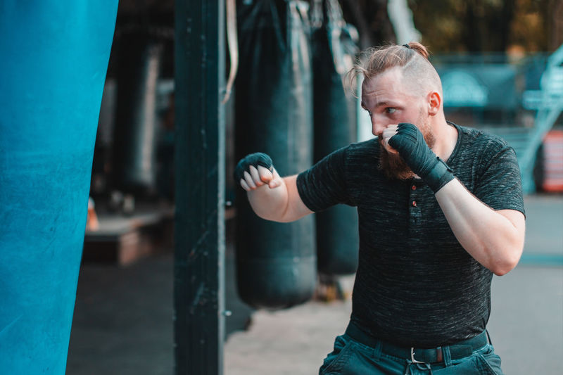 Young man practicing boxing while standing outdoors